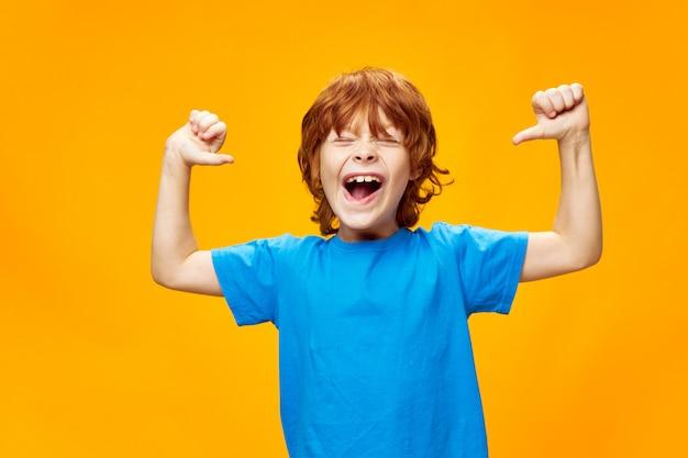 Um garoto ruivo com uma camiseta azul se divertindo em uma amarela e apontando para si mesmo