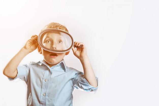 Um garoto surpreso em uma camisa azul, vestindo uma máscara subaquática para nadar