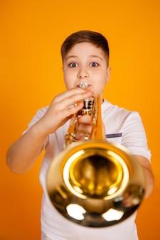 Um garoto toca trompete. menino bonito adolescente toca instrumento musical de trompete
