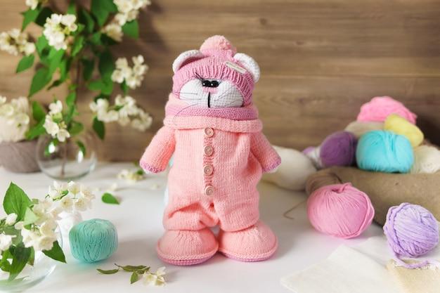 Um gato feito de fio de lã. brinquedo de pelúcia de malha artesanal sobre uma mesa de madeira.