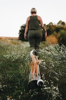 Um gato seguindo seu dono em uma fazenda