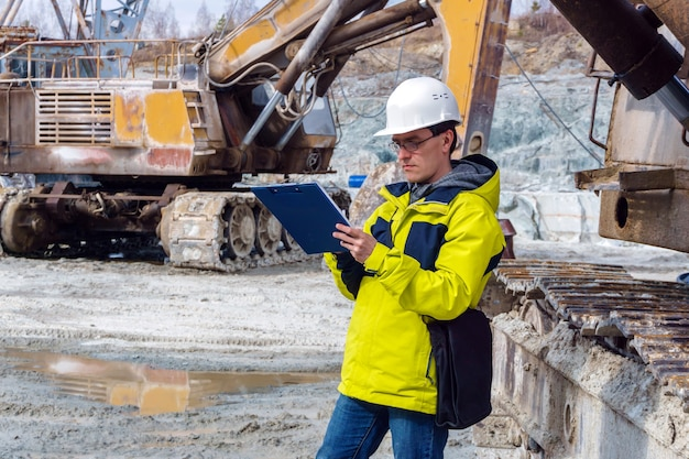 Um geólogo ou engenheiro de minas escreve algo em uma caixa de mapa em meio a uma pedreira com equipamentos de construção