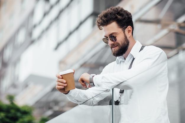 Um gerente barbudo, sério e elegante olhando para o relógio nas ruas da cidade perto do moderno centro de escritórios homem bebe café um funcionário olha para o relógio