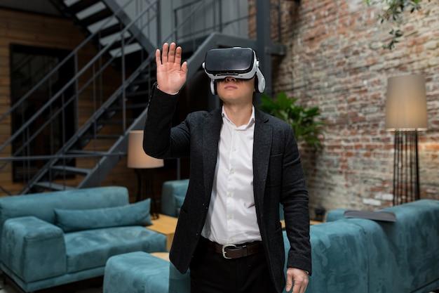 Um gerente com roupas formais usando óculos de realidade virtual vr passando por imagens on-line em um escritório moderno conceito de realidade aumentada pessoas e tecnologia