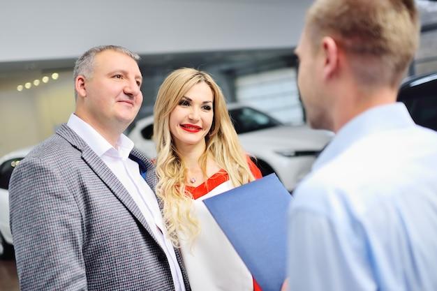 Um gerente consultor de um salão de automóveis ou loja de automóveis com um tablet nas mãos mostra alguns carros novos
