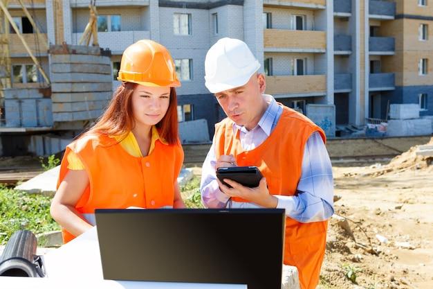 Um gerente em uma construção usando um capacete e conversando com sua colega
