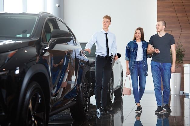 Um gerente profissional de concessionária mostrando um carro para clientes em uma concessionária