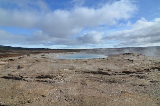 Um gerysir geotérmico quente em um campo na islândia