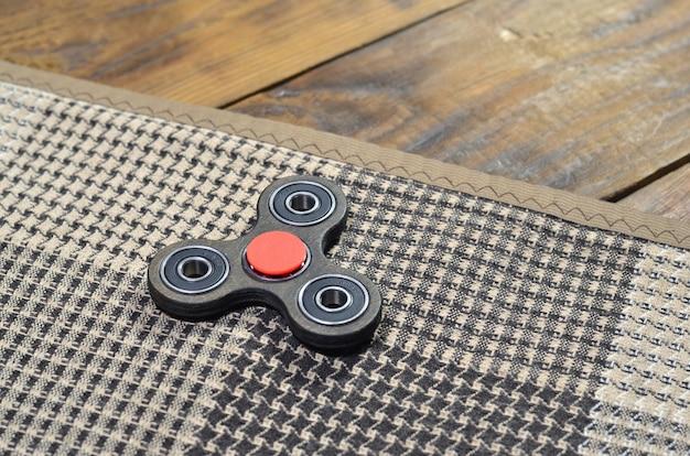 Um girador handmade de madeira raro encontra-se em uma manta quadriculado em uma superfície de madeira marrom do fundo. brinquedo de alívio de estresse na moda