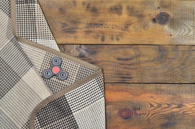 Um girador handmade de madeira raro encontra-se em uma manta quadriculado em uma superfície de madeira marrom do fundo.