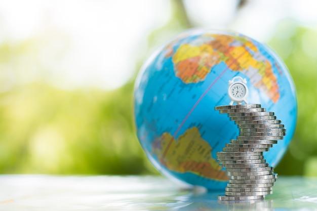 Um globo atrás de um relógio branco sobre a pilha de moedas. dinheiro, crescimento financeiro e empresarial c