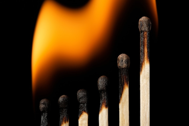 Um gráfico ascendente feito de fósforos de madeira, todos em chamas, isolados no preto