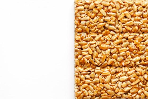 Um grande azulejo dourado de sementes de girassol, um bar em um melaço doce. kozinaki doces úteis e saborosos do oriente