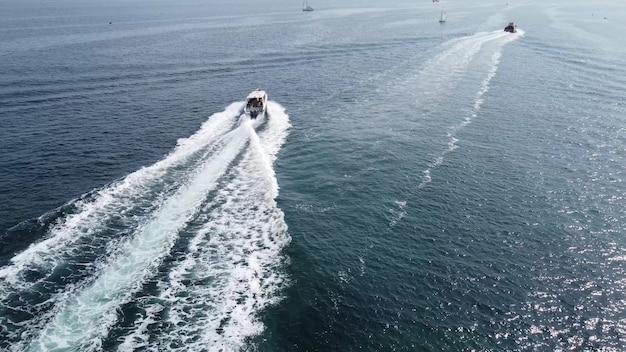 Um grande barco branco está se movendo em alta velocidade na água do mar azul