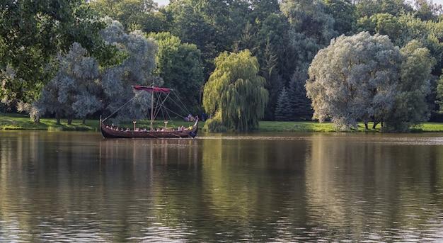 Um grande barco de madeira com turistas flutua no lago