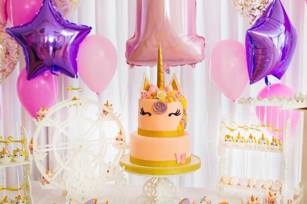 Um grande bolo e muitos doces na sala iluminada decorada com bolas infláveis