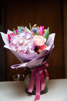Um grande buquê de flores coloridas de vários tipos está em um vaso de vidro transparente.