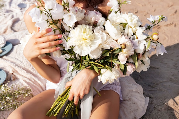 Um grande buquê de peônias e sinos brancos nas mãos de uma garota em um vestido leve