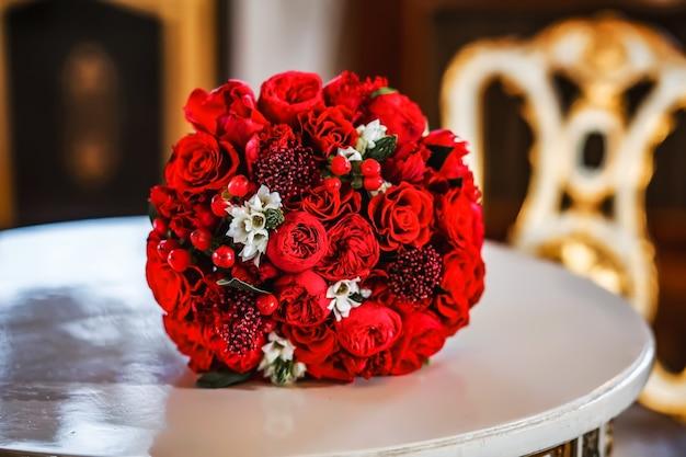 Um grande buquê de rosas vermelhas na mesa como um presente de noivado ou casamento no dia dos namorados
