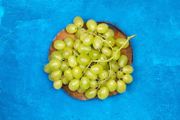 Um grande cacho de uvas verdes em um tronco de árvore e sobre um fundo azul