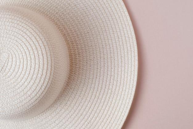 Um grande chapéu branco de senhora de praia em um fundo bege pastel. o conceito de férias, férias, viagens, vendas, sexta-feira negra.