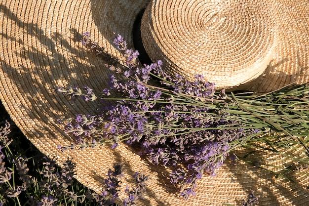 Um grande chapéu feito de palha natural com margens largas com um bouquet de lavanda em um campo de lavanda.