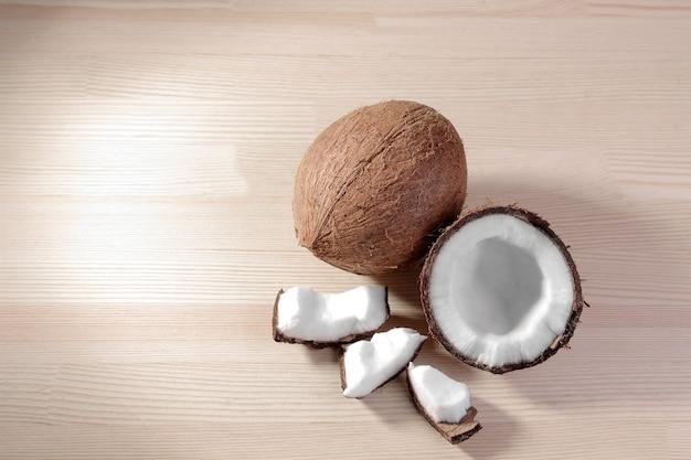 Um grande coco fresco e pedaços de coco sobre um fundo de madeira natural. vista do topo