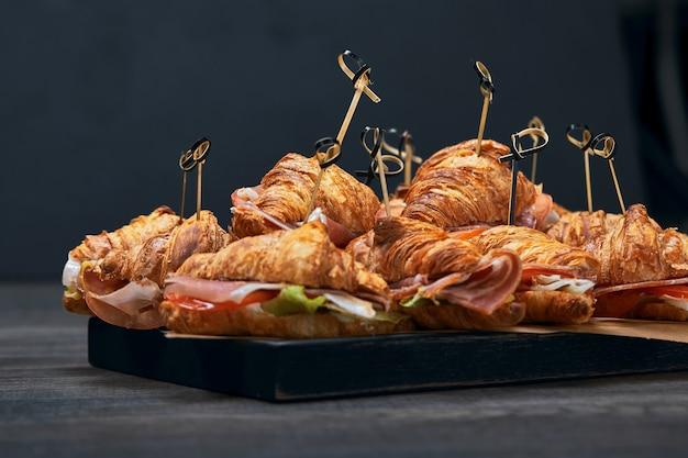 Um grande conjunto de muitos croissants com recheios diferentes dispostos sobre uma mesa em um fundo cinza. seth fast food. plano de fundo cinza, copie o espaço.