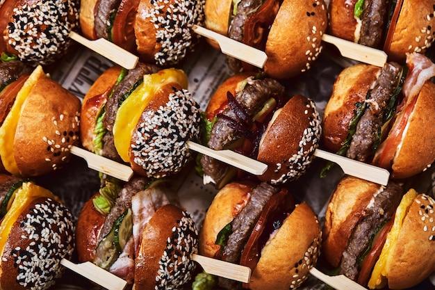 Um grande conjunto de muitos hambúrgueres, cheesburgers maravilhosamente dispostos.