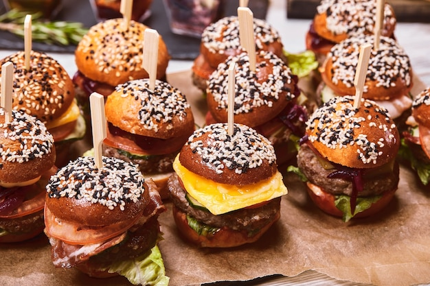 Um grande conjunto de muitos hambúrgueres, cheeseburgers dispostos sobre a mesa. seth fast food. fundo de comida, copie o espaço.
