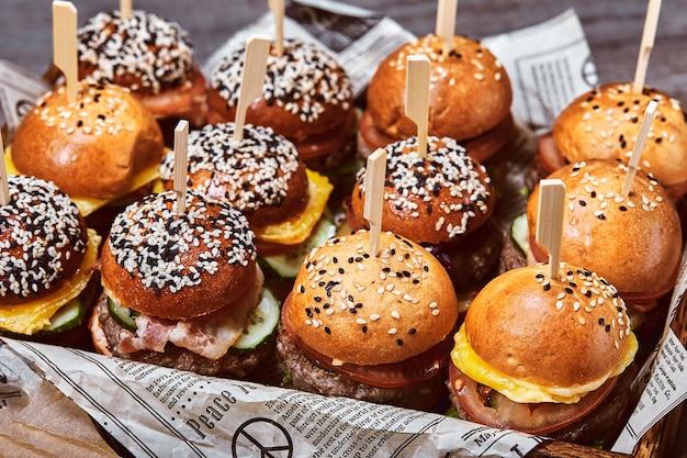Um grande conjunto de muitos hambúrgueres, cheeseburgers dispostos sobre a mesa. seth fast food. parede de comida, cópia espaço.