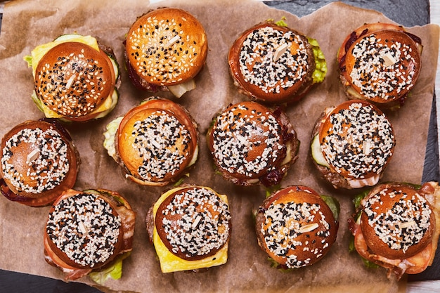 Um grande conjunto de muitos hambúrgueres, cheeseburgers maravilhosamente dispostos. patern de um grande número de hambúrgueres. parede de alimentos