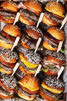 Um grande conjunto de muitos hambúrgueres, cheeseburgers maravilhosamente dispostos.