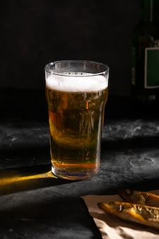 Um grande copo de cerveja light e dois peixes secos