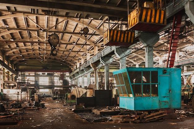 Um grande galpão industrial abandonado está esperando para ser demolido, um guindaste industrial.