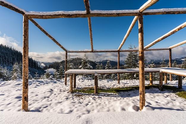Um grande gazebo descoberto no topo da montanha fica em um prado branco coberto de neve banhado pela luz do sol frio e brilhante dos cárpatos