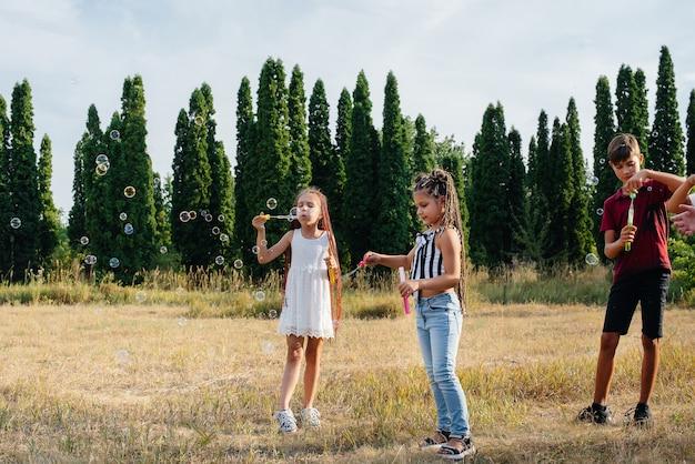 Um grande grupo de crianças alegres brinca no parque e infla bolhas de sabão. jogos em um acampamento infantil.