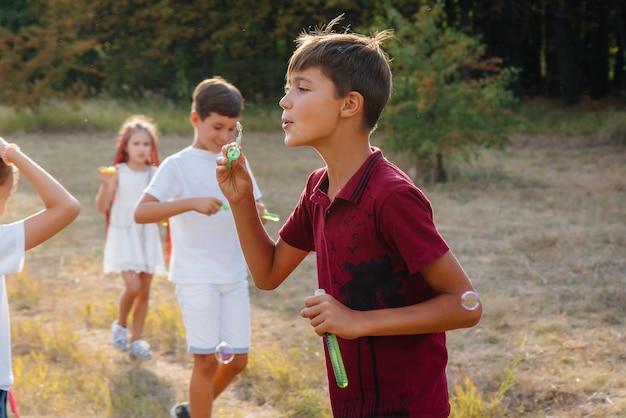 Um grande grupo de crianças alegres brinca no parque e infla bolhas de sabão