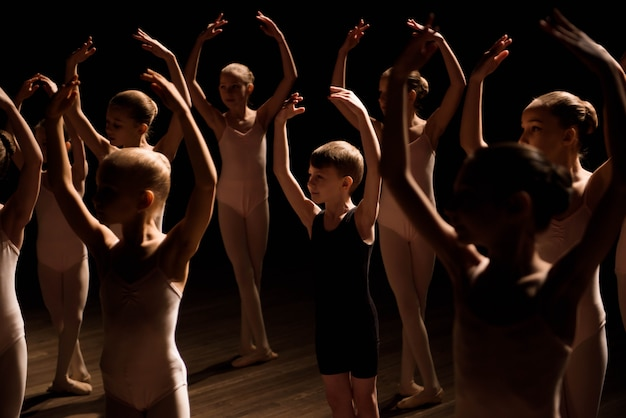 Um grande grupo de crianças ensaiando e dançando o balé