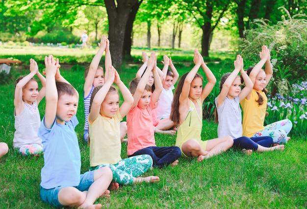 Um grande grupo de crianças envolvidas em yoga no parque, sentado na grama.