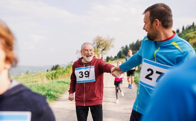 Um grande grupo de pessoas ativas de várias gerações participando de uma competição de corrida na natureza.