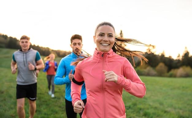 Um grande grupo de pessoas atravessa o país correndo na natureza ao pôr do sol.