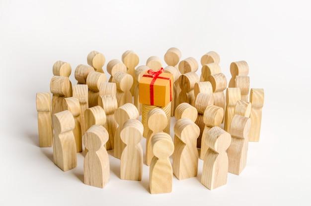 Um grande grupo de pessoas rodeia uma caixa com um presente.