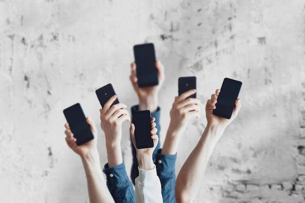 Um grande grupo de pessoas segura um dispositivo de telefone digital, muitas mãos humanas