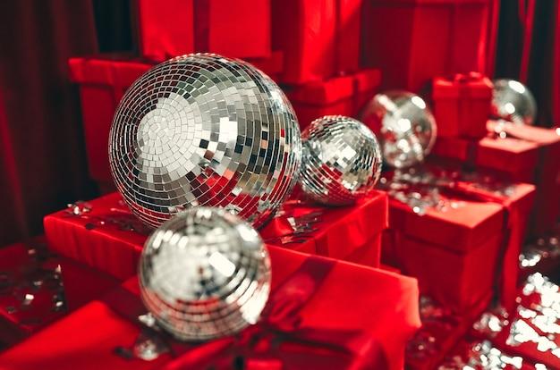 Um grande grupo de presentes de natal embrulhados para presente em papel de embrulho vermelho colorido com fitas e laços, sobre um fundo vermelho com bolas de discoteca e metafano. presente de ano novo photozone