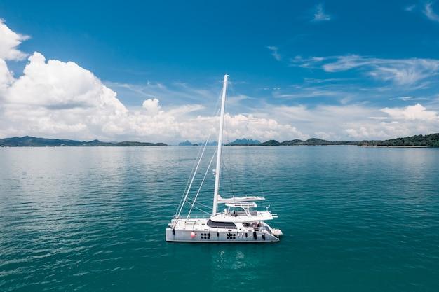 Um grande iate branco flutuando no quente oceano azul. barcos à vela. tempo de descanso. férias caras. foto de um quadrocopter. natureza tropical. riqueza rica.