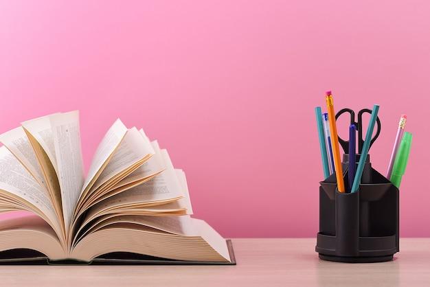 Um grande livro grosso com as páginas espalhadas como um leque e um suporte com canetas, lápis e tesoura sobre a mesa em um fundo rosa.