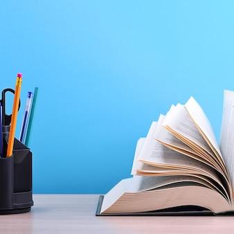 Um grande livro grosso com as páginas espalhadas como um leque e um suporte com canetas, lápis e tesoura sobre a mesa, sobre um fundo azul.