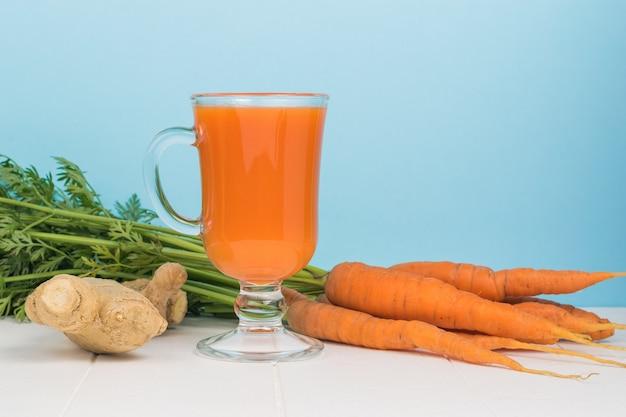 Um grande monte de cenoura, gengibre e vitaminas em uma mesa branca.