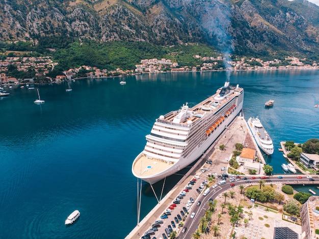 Um grande navio de cruzeiro atracado na baía de kotor, montenegro. vista aérea em um dia ensolarado.